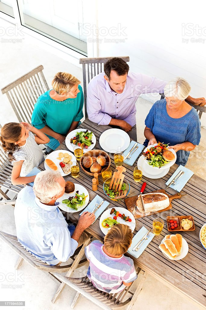 Three Generation Family Having Food At Table On Porch royalty-free stock photo