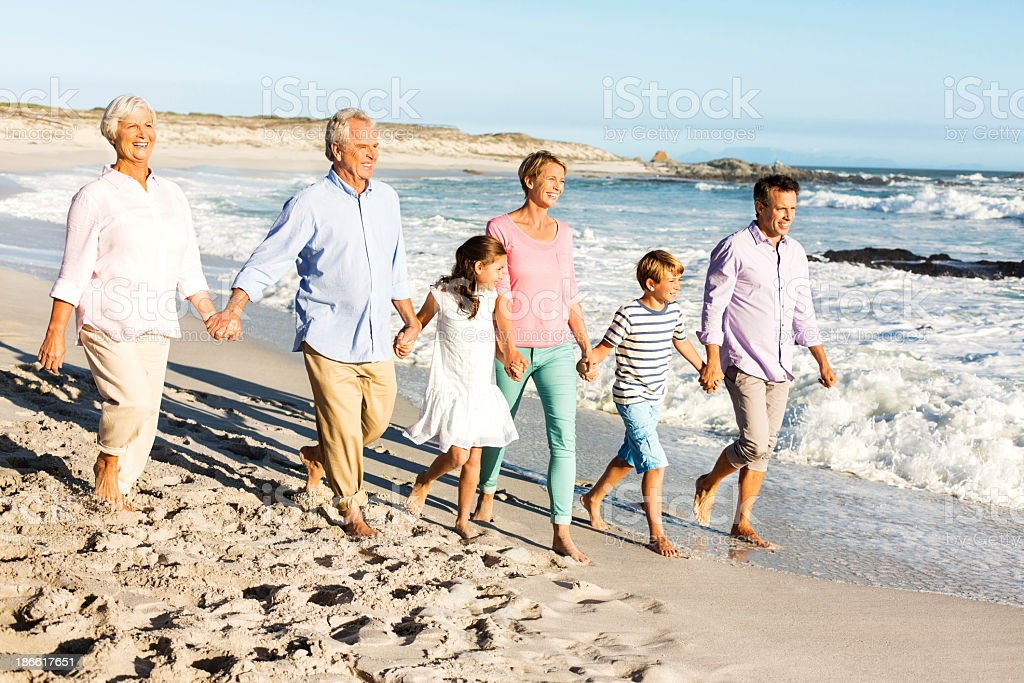 Three Generation Family Holding Hands While Walking On Beach stock photo