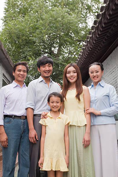 familie mit drei generationen in einem courtyard - hofkleider stock-fotos und bilder