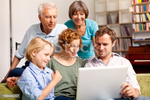 A lovely family with three generation is making plans for the future, looking on a laptop in an luminous indoor scene with out of focus bookshelf in the background. Selective focus on young adults.