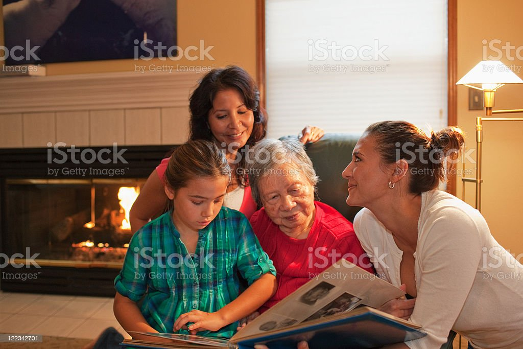 Three generation family looking at photo album stock photo