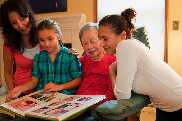 three generation family looking at photo album - senior fotoboek stockfoto's en -beelden