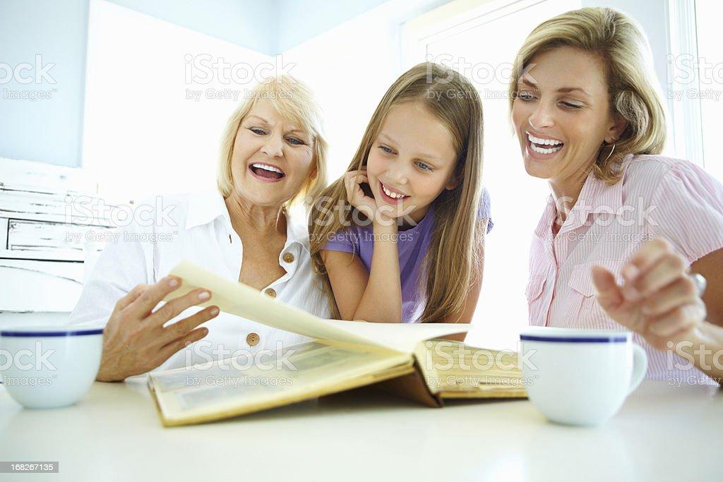 Three generation family looking at photo album royalty-free stock photo
