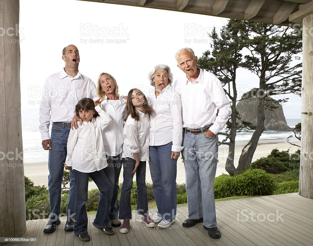 Three generation family on deck pulling funny faces, portrait royalty free stockfoto