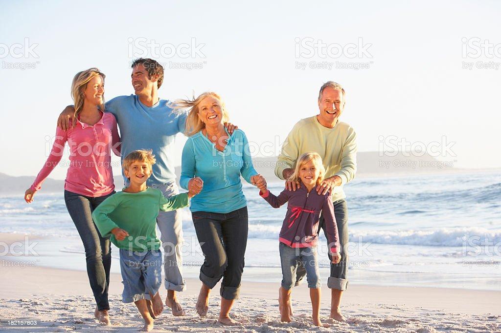 Three Generation Family On Holiday Running Along Beach royalty-free stock photo
