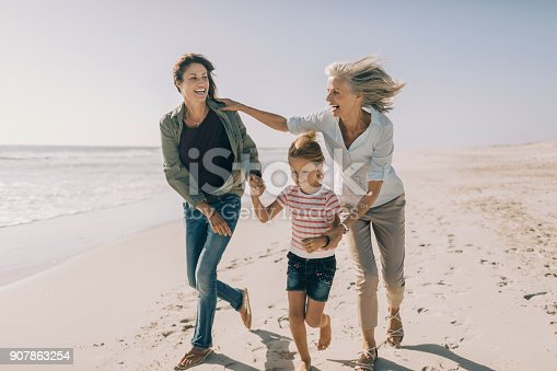 Close up of three generation family enjoying time on the beach