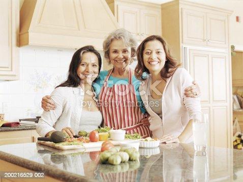 916556066 istock photo Three generation family preparing food in kitchen, portrait 200216529-002