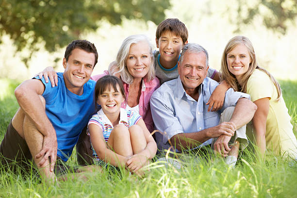 Three Generation Family Relaxing In Summer Field stock photo