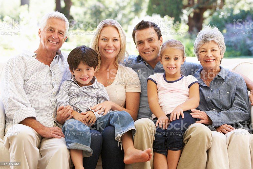 Three Generation Family Sitting On Sofa At Home stock photo