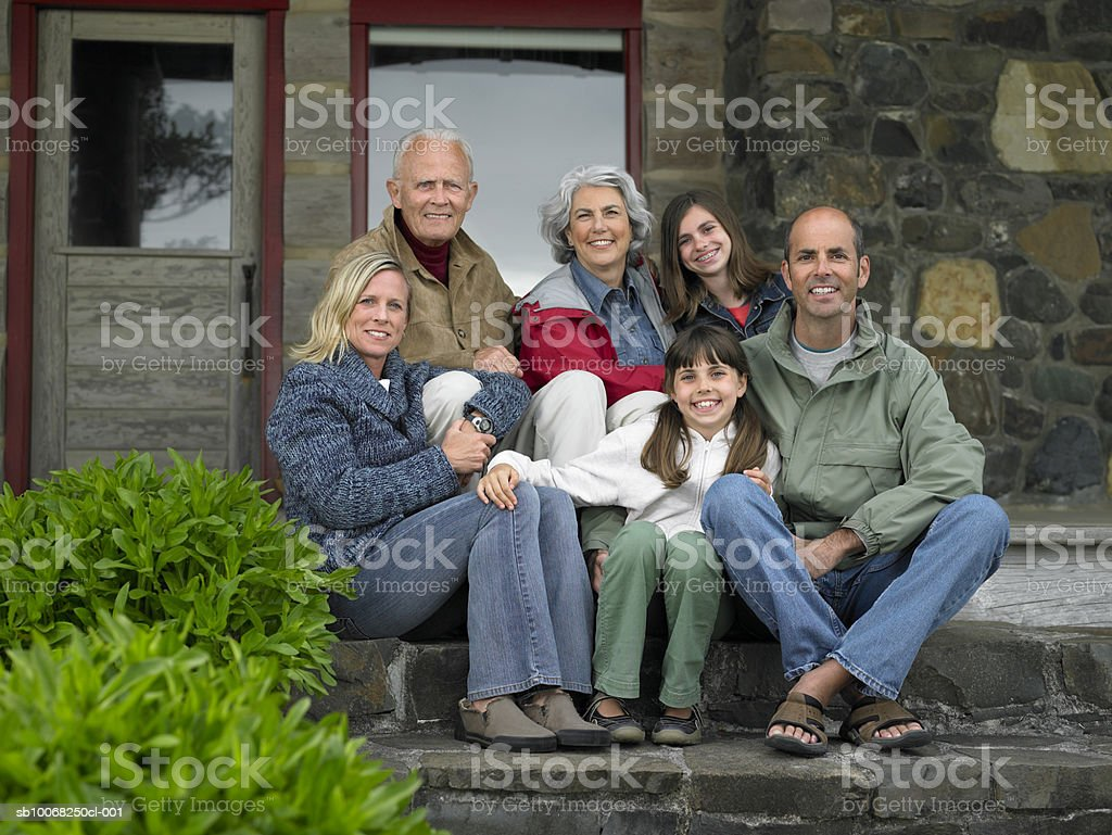 Three generation family sitting on steps in front of house, smiling portrait royalty-free stock photo
