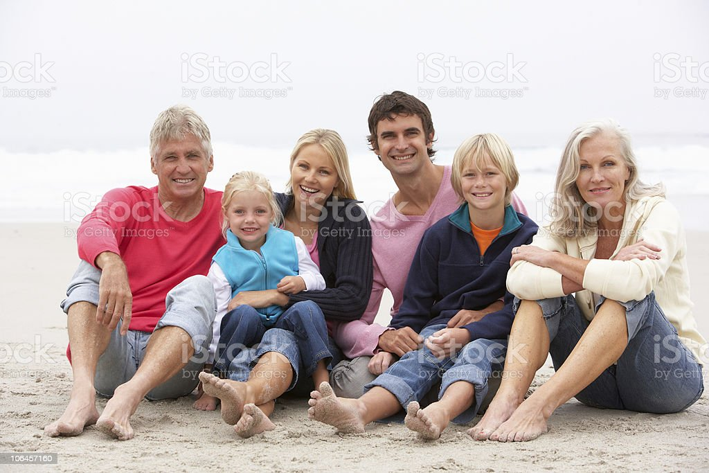 Three Generation Family Sitting On Winter Beach Together royalty-free stock photo