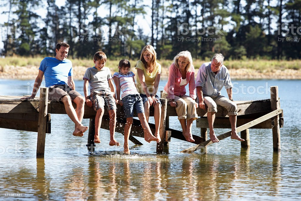 Three Generation Family Sitting On Wooden Jetty stock photo