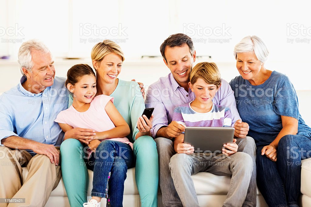 Three Generation Family Smiling Using Smart Phone And Tablet royalty-free stock photo
