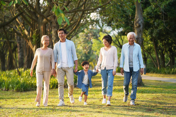 three generation family walking outdoors in park stock photo