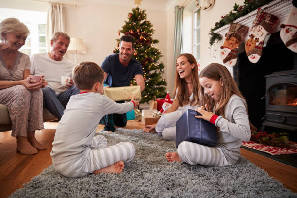 three generation family wearing pajamas in lounge at home opening gifts on christmas day - regalo natale foto e immagini stock
