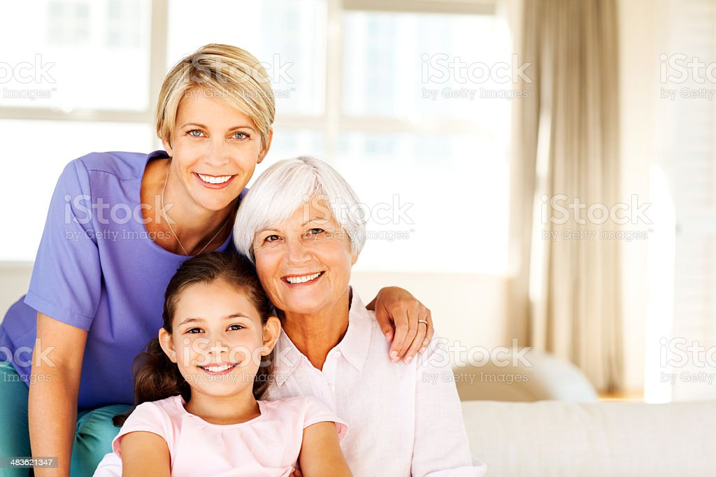 Three Generation Females Smiling Together In Living Room stock photo