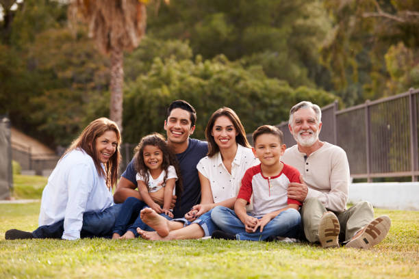 Three generation Hispanic family sitting on the grass in the park smiling to camera, selective focus Three generation Hispanic family sitting on the grass in the park smiling to camera, selective focus monkeybusinessimages stock pictures, royalty-free photos & images