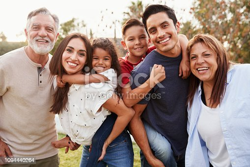 istock Three generation Hispanic family standing in the park, smiling to camera, selective focus 1094440264