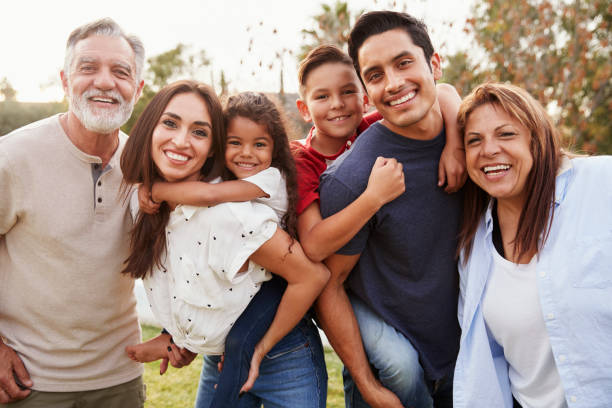 Three generation Hispanic family standing in the park, smiling to camera, selective focus stock photo