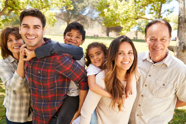 three generation multi ethnic family portrait in a park - multi generation family stock photos and pictures