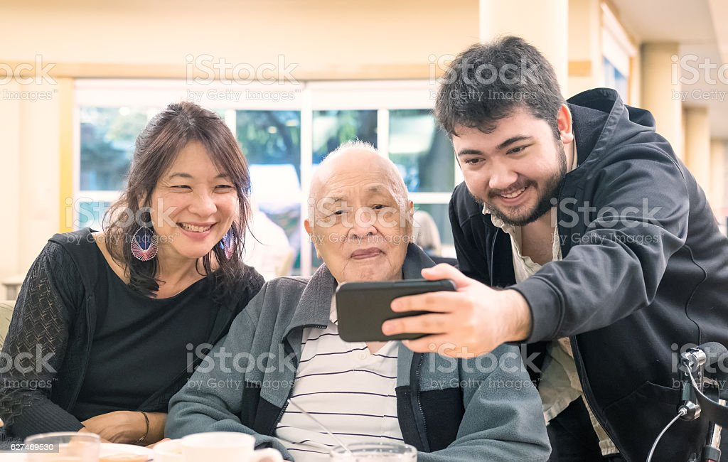 Three Generation, Multi-Ethnic Asian, Eurasian Family Taking Selfie with Smartphone stock photo