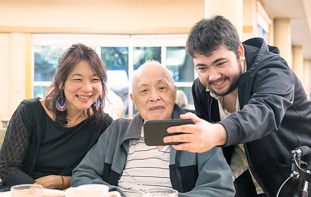 Three Generation, Multi-Ethnic Asian, Eurasian Family Taking Selfie with Smartphone Asian grandfather and daughter with Eurasian grandson taking selfie after a meal together.  Walker in foreground. old mother son asian stock pictures, royalty-free photos & images