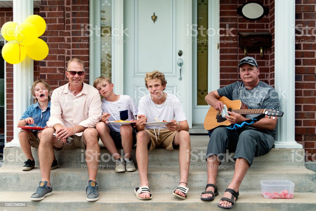 Three generation of males sitting on home porch. stock photo