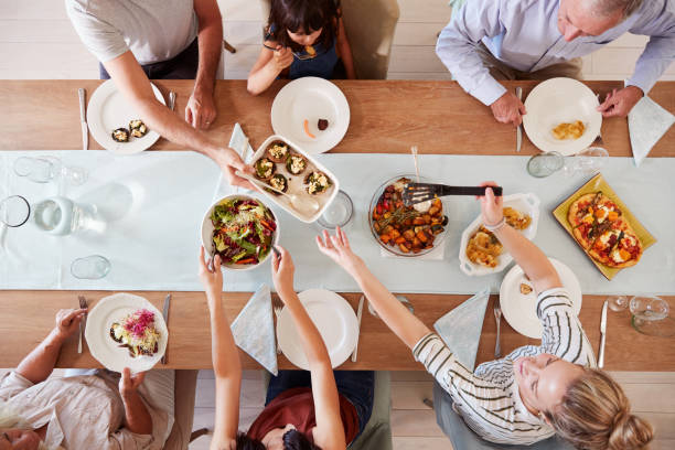 three generation white family sitting at a dinner table together serving a meal, overhead view - jantar refeições imagens e fotografias de stock