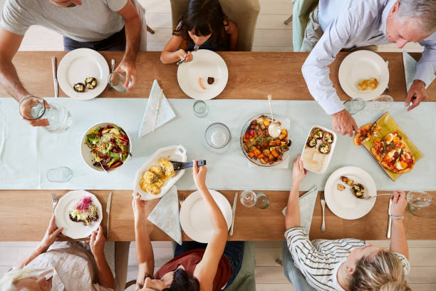 Three generation white family sitting at a dinner table together serving a meal, overhead view Three generation white family sitting at a dinner table together serving a meal, overhead view dining table stock pictures, royalty-free photos & images