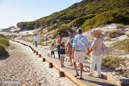 istock Three generation white family walking together along a wooden promenade on a beach, full length 1162303109