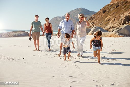 Three generation white family walking together on a sunny beach, kids running ahead