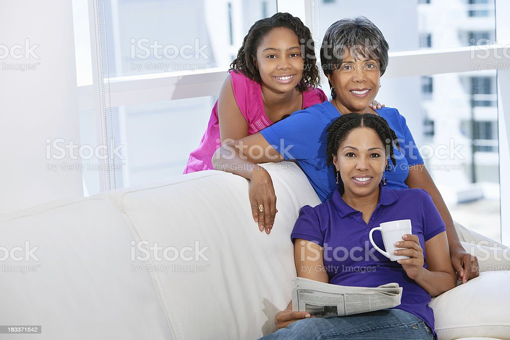 Three generational females sitting on couch smiling at camera stock photo
