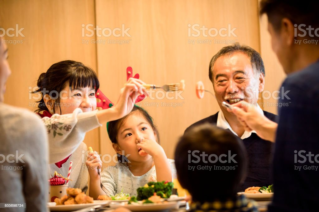 Three generations family enjoying Christmas dinners stock photo