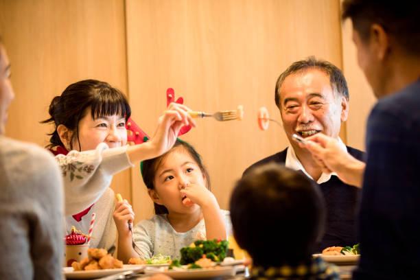 drei generationen familie genießen weihnachtsessen - weihnachten japan stock-fotos und bilder