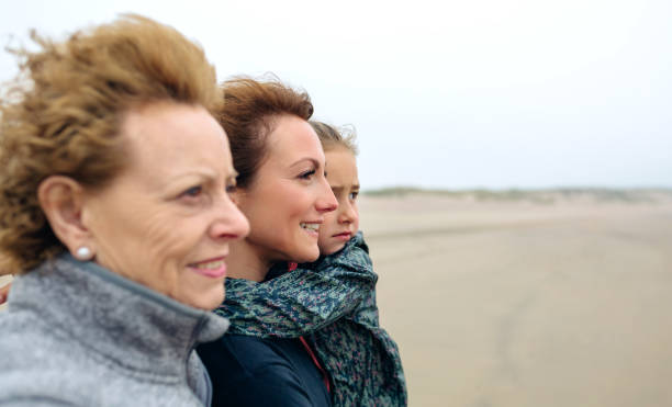 three generations female looking at sea - multi generation family stock photos and pictures