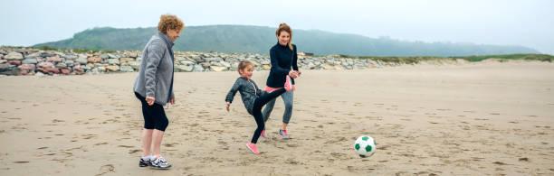 drei generationen weiblich spielen fußball am strand - granny legs stock-fotos und bilder