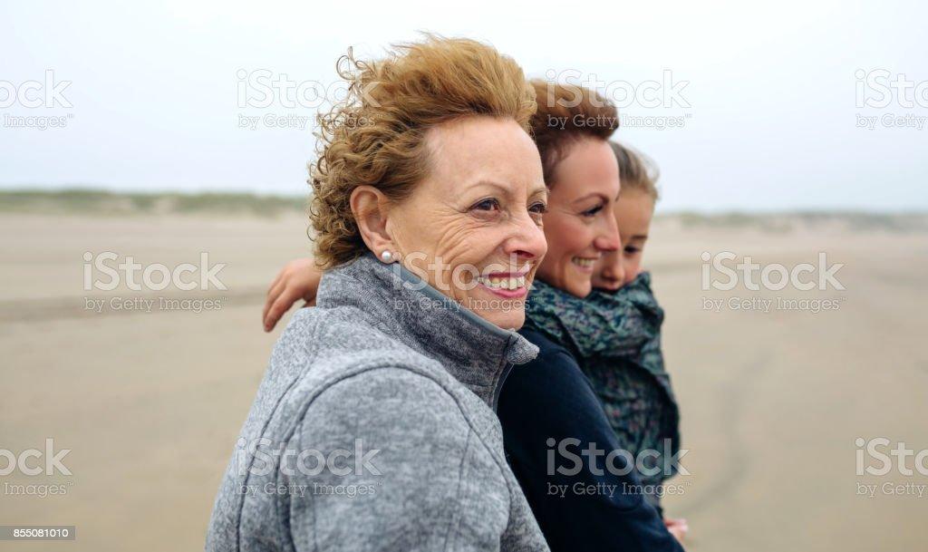 Three generations female walking on the beach stock photo