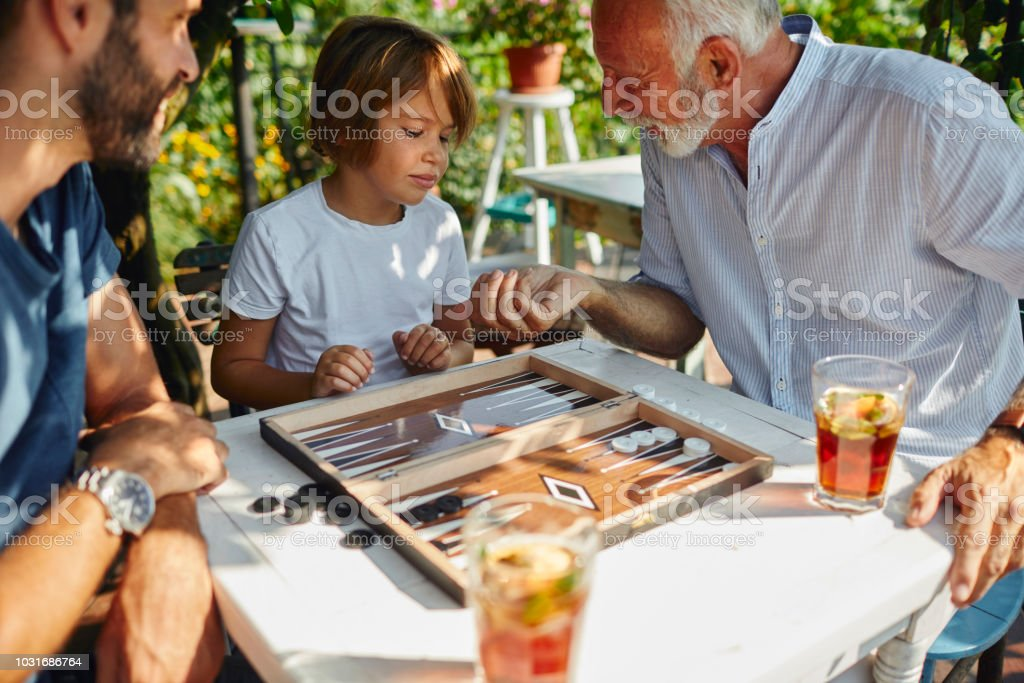 Three Generations Males Playing Backgammon Together stock photo