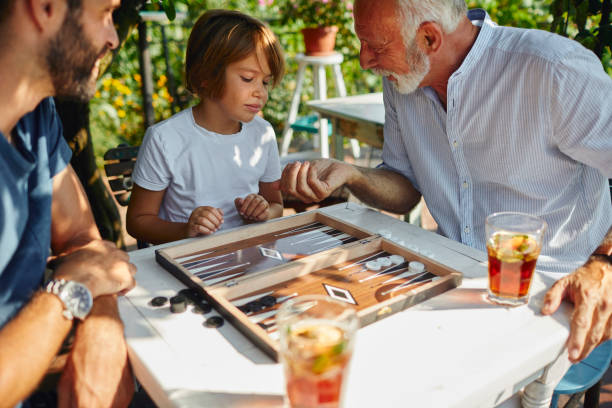 three generations males playing backgammon together - backgammon stock pictures, royalty-free photos & images