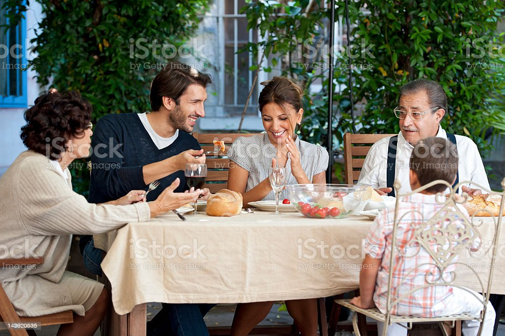 Three generations of a family eating in the garden royalty-free stock photo