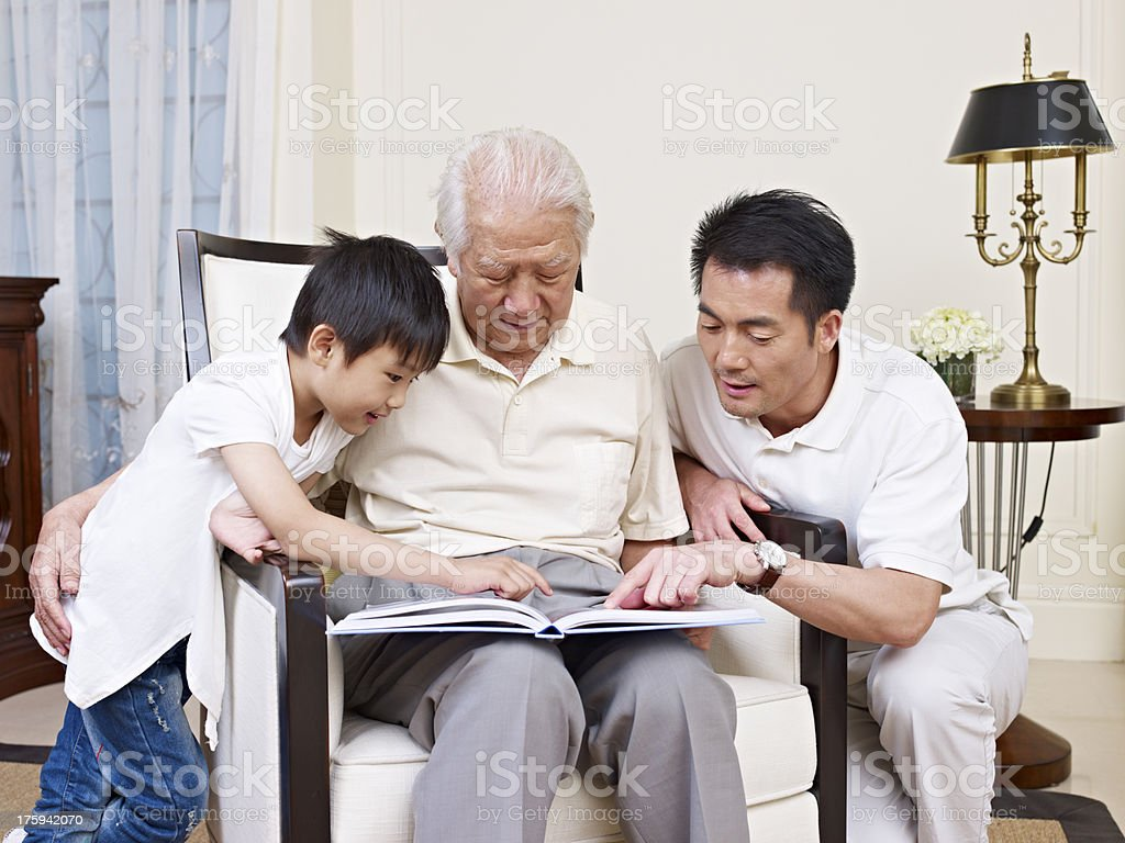 Three generations of a family looking at a book stock photo
