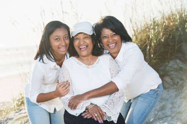 Three generations of black women posing on beach stock photo