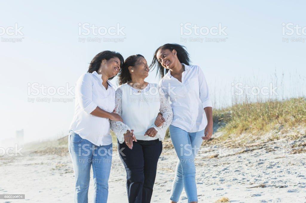 Three generations of black women walking on beach stock photo