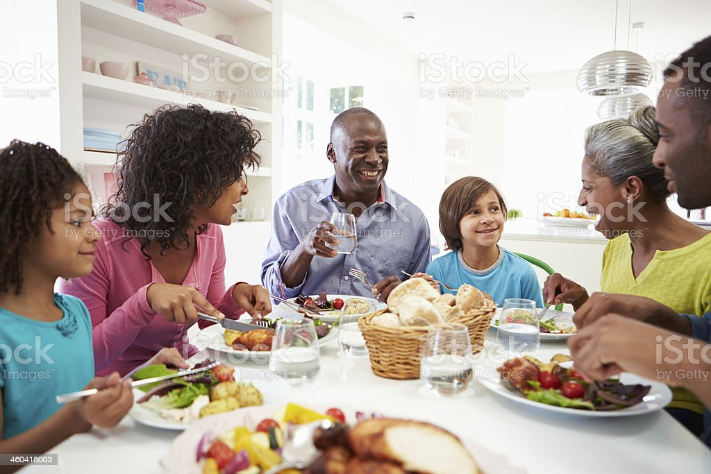 Three generations of family enjoy a meal together at home stock photo