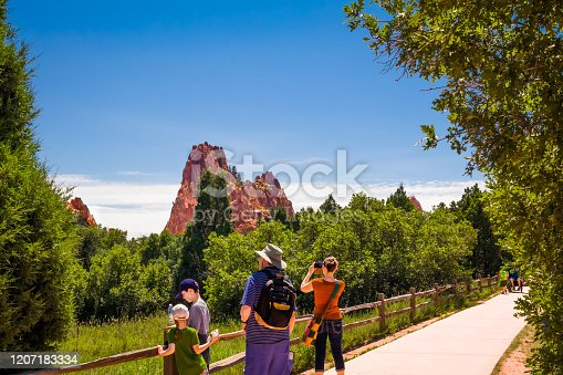 Beautiful view of Garden of the Gods park in Colorado Springs, Colorado,   in summer; three generations of family are enjoying the view; middle-aged woman taking photos with her smartphone