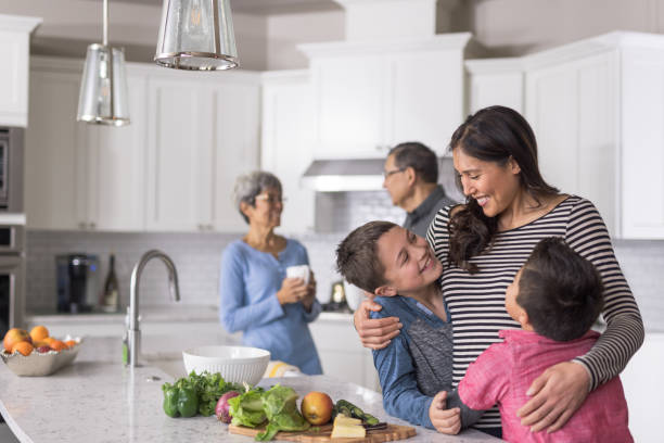 Three generations of family making lunch together in a modern kitchen stock photo