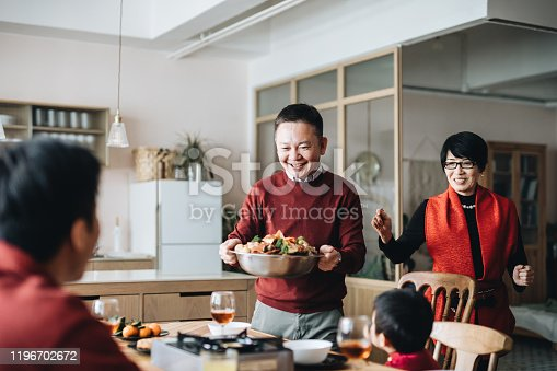 Three generations of joyful Asian family celebrating Chinese New Year and grandparents serving traditional Chinese poon choi on reunion dinner