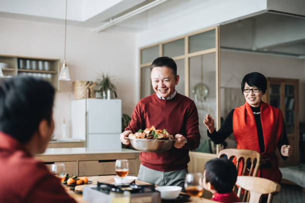 three generations of joyful asian family celebrating chinese new year and grandparents serving traditional chinese poon choi on reunion dinner - family gatherings stock pictures, royalty-free photos & images