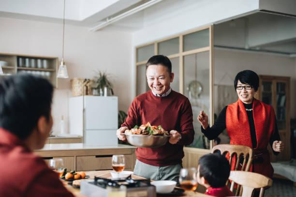 trzy pokolenia radosnej azjatyckiej rodziny świętującej chiński nowy rok i dziadków serwujących tradycyjne chińskie poon choi na kolacji reunion - kolacja spotkanie towarzyskie zdjęcia i obrazy z banku zdjęć