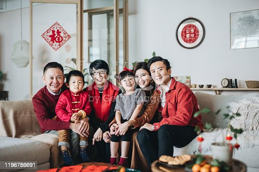 Three generations of joyful Asian family embracing and celebrating Chinese New Year together